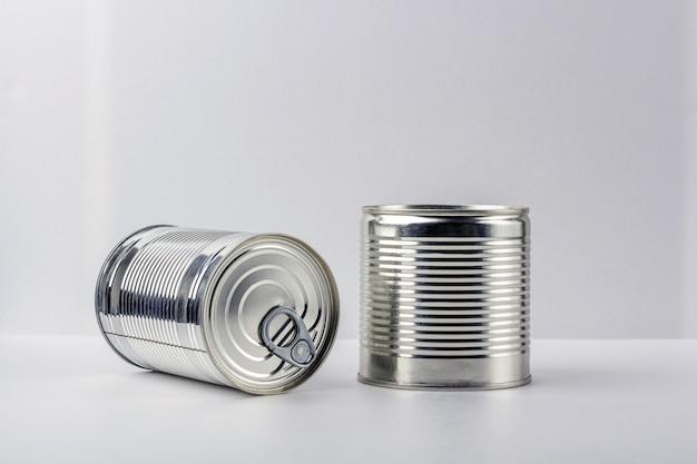 Dwa blaszana puszka na białym tle. zaopatrzenie w żywność podczas kwarantanny i samoizolacji koronawirusa. dostawa żywności, darowizna, wsparcie wolontariuszy. skopiuj miejsce na tekst