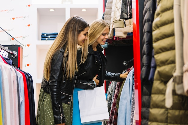 Dwa blondynki młodej kobiety patrzeje odziewa w zakupy sklepie