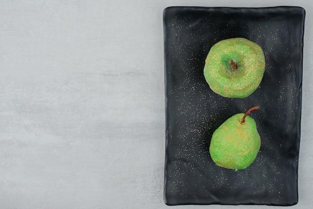 Dwa błyszczące jabłka na ciemnym talerzu na białej powierzchni.