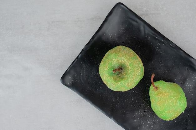 Dwa błyszczące jabłka na ciemnym talerzu na białej powierzchni