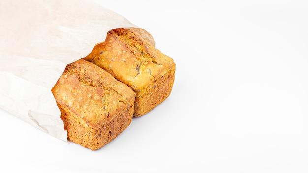 Dwa bochenka pełnoziarnisty chleb w eco torbie na białym tle. świeżo upieczony domowy chleb kwadratowy. koncepcja żywności ekologicznej i wegetariańskiej. skopiuj miejsce na tekst
