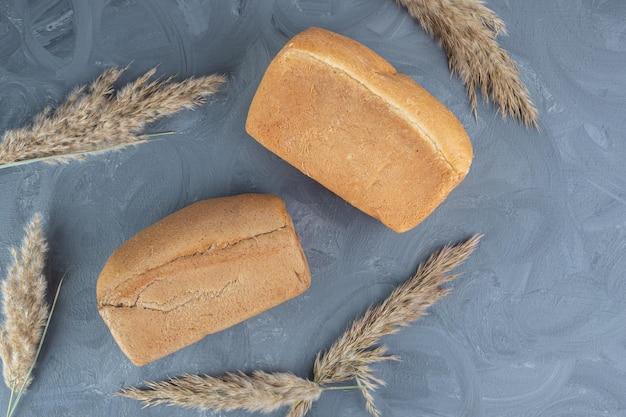 Dwa bochenki chleba otoczone suszonymi łodygami trawy piórkowej na marmurowym stole.