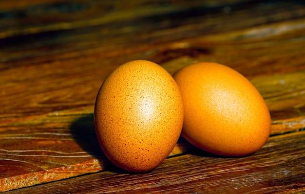 Dwa brązowe jaja kurze na starym stole z drewna tekowego, w płytkiej ostrości