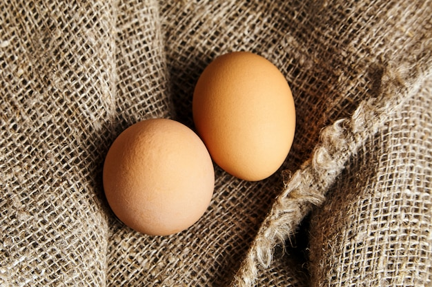 Dwa brązowe jaja kurze na włóknie worze