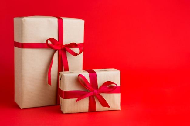 Dwa brązowe pudełka z czerwonymi wstążkami na czerwonym tle. prezent na boże narodzenie, walentynki lub urodziny.
