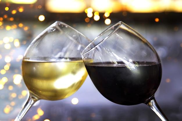 Dwa brzęczące kieliszki z czerwonym i białym winem przed bokeh tłem ze światłami. świąteczna koncepcja.