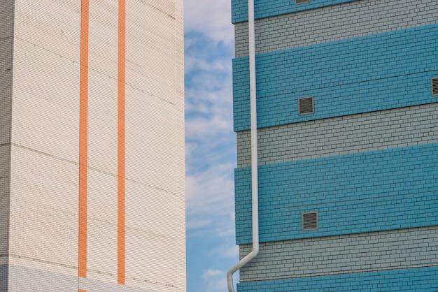 Dwa budynki. budynek do sklepu, warsztatu, garażu i innych potrzeb przemysłowych. biały mur z metalowymi oknami i niebieskimi cegłami zbliżenie z białymi rurami spustowymi z miejsca na kopię.