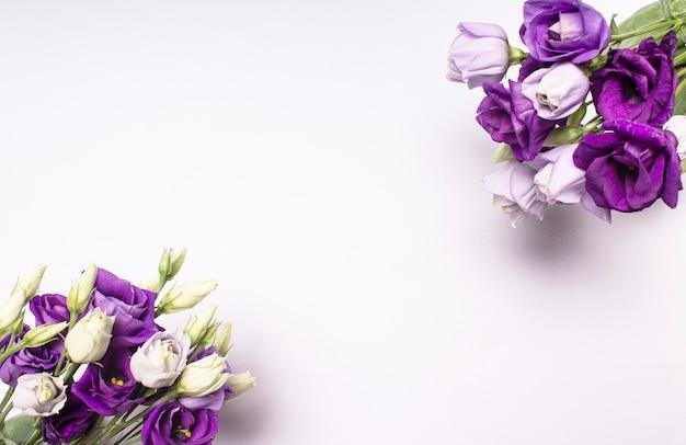 Dwa bukiety fioletowych i białych kwiatów w rogach karty