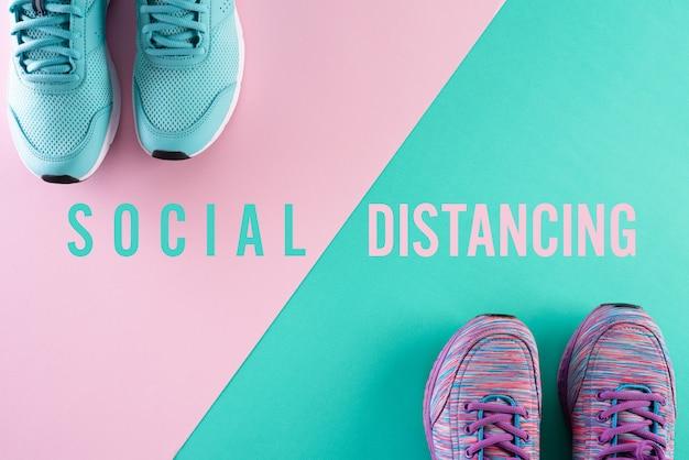 Dwa buty do społecznej koncepcji dystansowania na zielonej różowej pastelowej ścianie
