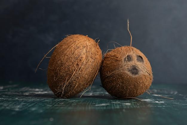 Dwa całe kokosy na marmurowym stole.