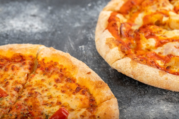 Dwa całe kurczaka pizza umieszczone na kamiennym tle.