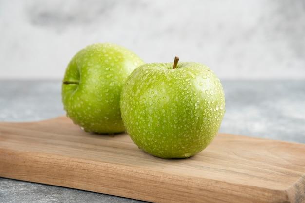 Dwa całe zielone jabłka na drewnianym talerzu na marmurowym stole.