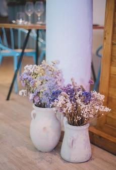 Dwa ceramiczne wazony z polnymi kwiatami