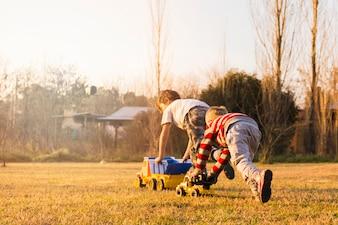 Dwa chłopiec bawić się z zabawkarskimi pojazdami na zielonej trawie
