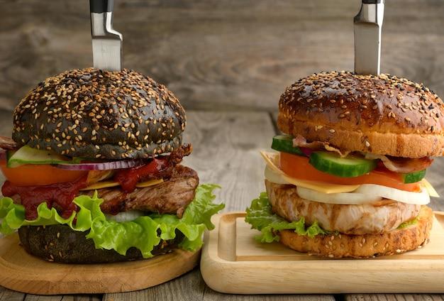 Dwa cheeseburgery z warzywami i stek mięsny na drewnianej desce, kanapkę przekłuwa się nożem