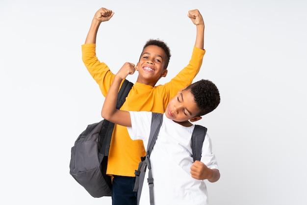 Dwa chłopiec amerykanina afrykańskiego pochodzenia ucznia nad odosobnionym białym tłem