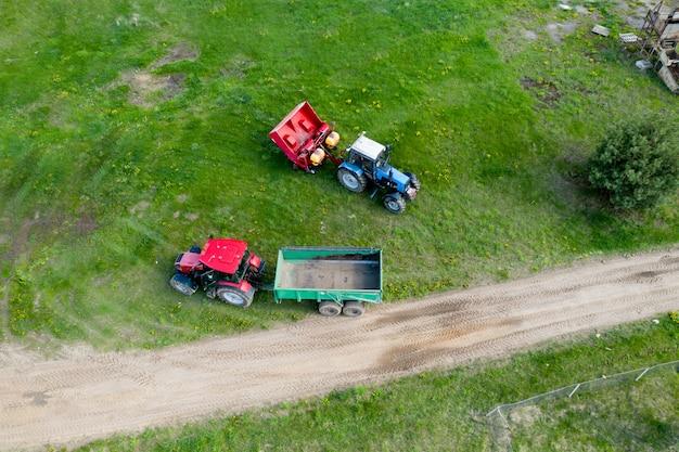 Dwa ciągniki w widoku z góry na podwórku rolnika.