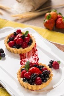 Dwa ciasta owocowe z malinami, jagodami i morwy w talerzu nad stołem.