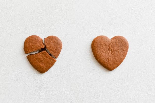 Dwa ciasteczka w kształcie serca, jeden z nich jest złamany na białym tle. pęknij ciasteczka w kształcie serca jako pojęcie zrywania i kończenia związków, nieodwzajemnionej miłości. nieodwzajemniona koncepcja miłości .. valenti