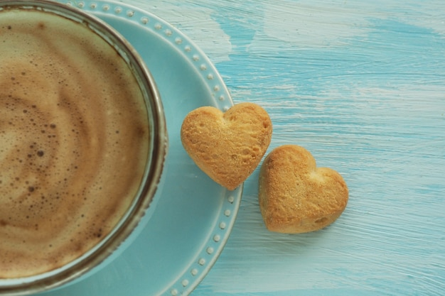 Dwa ciasteczka w kształcie serca na spodeczku przy filiżance kawy.