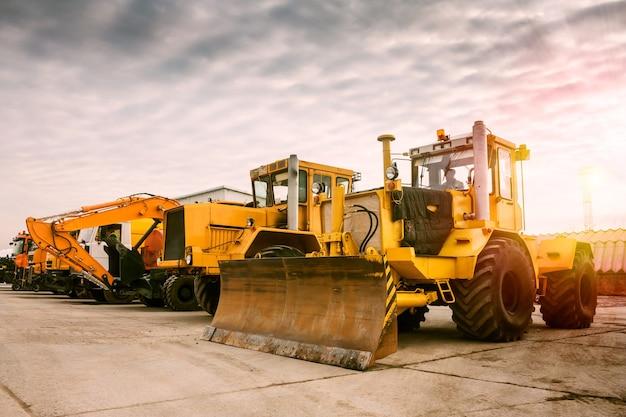 Dwa ciężkie ciągniki kołowe, jedna koparka i inne maszyny budowlane w porannym słońcu