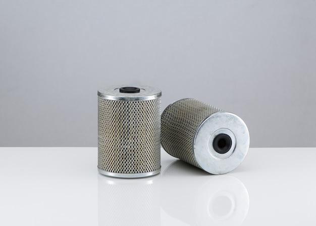 Dwa cylindryczne filtry samochodowe na białym tle z odbiciem