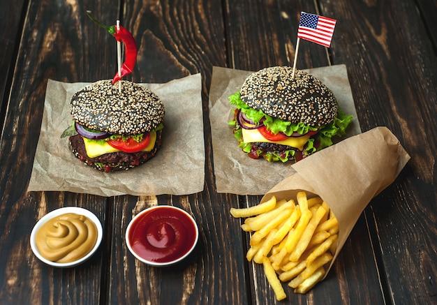 Dwa czarne hamburgery z amerykańską flagą, sałatą, pomidorem i frytkami. drewniane tła