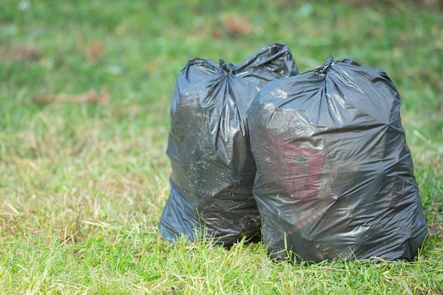 Dwa czarne worki na śmieci postawione na podłodze z trawy