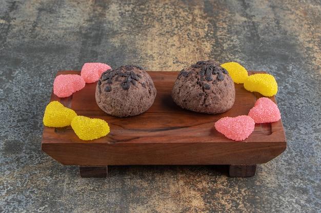 Dwa czekoladowe ciasteczka i cukierki marmoladowe na drewnianym talerzu