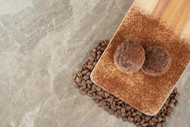 Dwa czekoladowe ciasteczka na drewnianym talerzu z ziarnami kawy