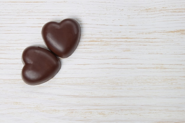 Dwa czekoladowe cukierki serca na białym tle drewniane z kropkami, walentynki, z bliska z miejsca na kopię