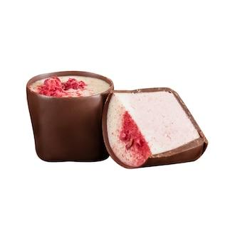 Dwa czekoladowe cukierki z czerwonymi owocami posypane na wierzchu, odizolowane na białej powierzchni