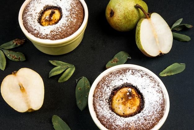 Dwa czekoladowe desery z gruszką na czarnym kamiennym stole, widok z góry