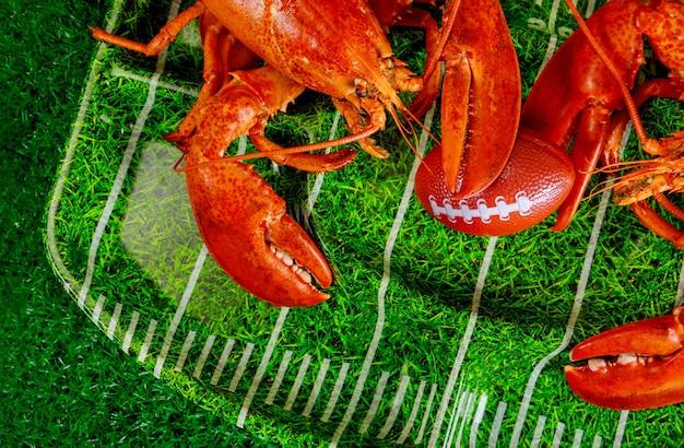 Dwa czerwone homary gotowane na zielonym talerzu z piłką nożną