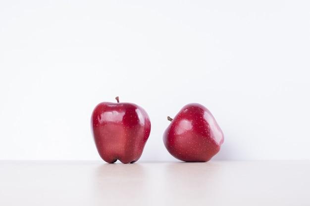 Dwa czerwone jabłka na białej powierzchni.