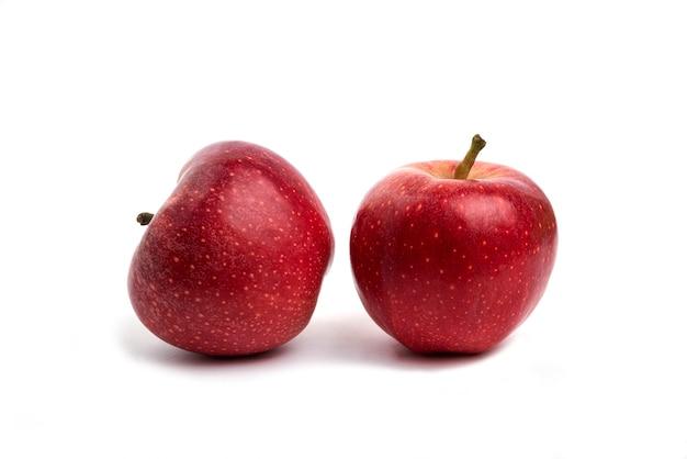 Dwa czerwone jabłka na białym tle.