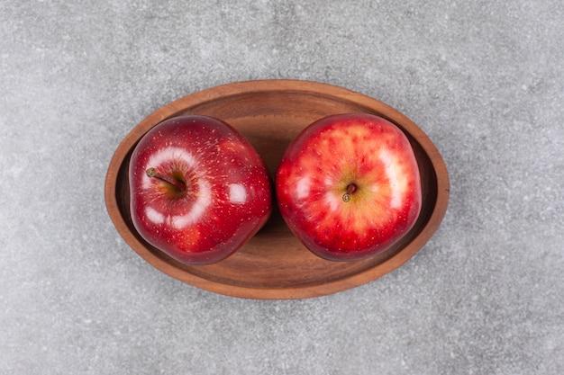 Dwa czerwone jabłka na drewnianym talerzu
