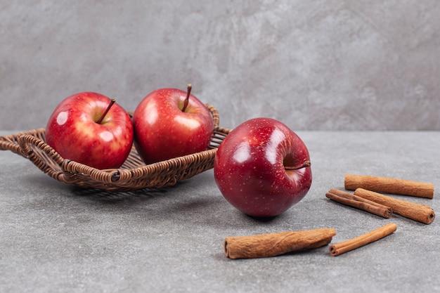 Dwa czerwone jabłka w drewnianym koszu z laskami cynamonu