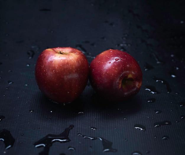 Dwa czerwone jabłka z kroplami wody, kładzione na mokrej powierzchni, wokół rozmyte światło