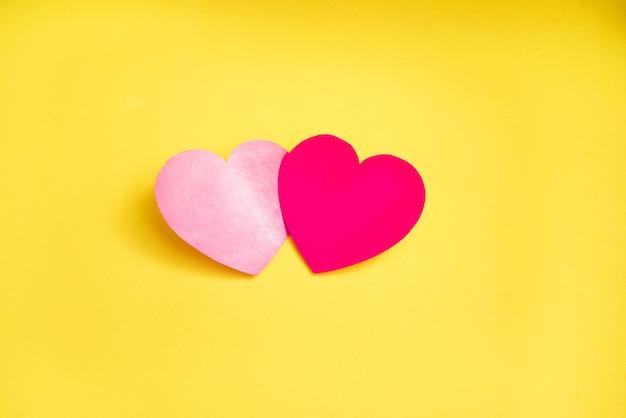 Dwa czerwone serca kochanków razem na żółtym tle.