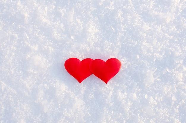 Dwa czerwone serca leżące na białym czystym śniegu w słoneczny zimowy dzień.