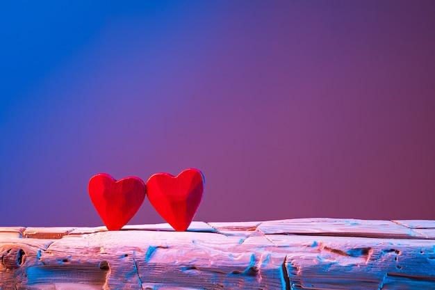 Dwa czerwone serca na ręcznie ciosanej belce wibrujących neonów. obraz na walentynki