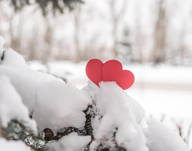 Dwa czerwone serca w zimowym lesie na śniegu. romans i miłość w walentynki
