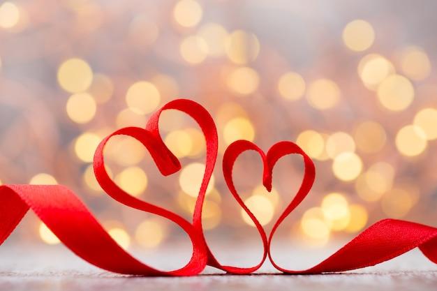 Dwa czerwone serca wstążki. walentynki kartkę z życzeniami.