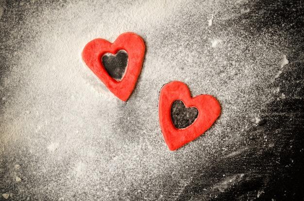 Dwa czerwone serca wycięte z ciasta na posypanym mąką stole, czarny stół, copyspace. widok z góry
