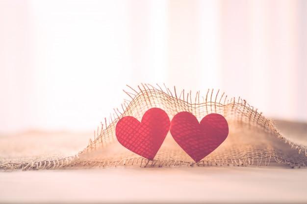Dwa czerwone serce z workowym materiałem na walentynki