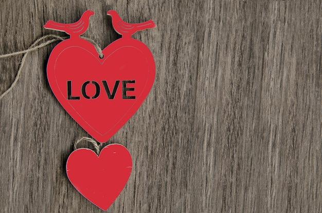 Dwa czerwonego kształta serca z dwa gołębiami na drewnianym tle