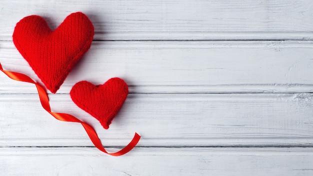 Dwa czerwonego serca i faborek na drewnianym białym tle z kopii przestrzenią