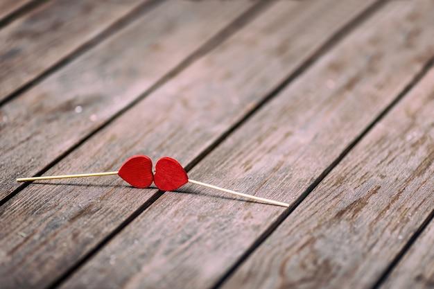 Dwa czerwonego serca kształtują na kiju nad drewnianym tłem. koncepcja valentine