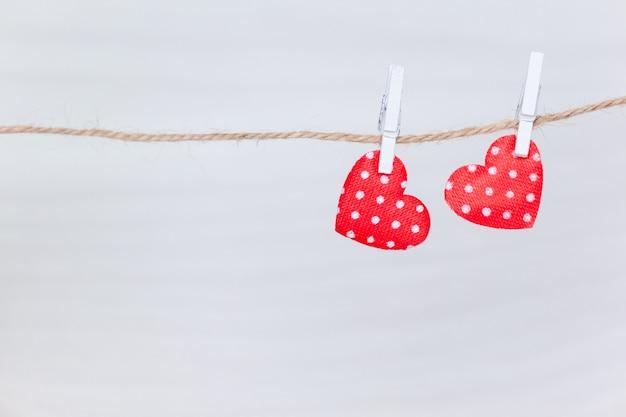 Dwa czerwonego serca wiesza na nici na białym drewnianym tle. walentynki, miłość, koncepcja ślubu. leżał płasko, widok z góry.